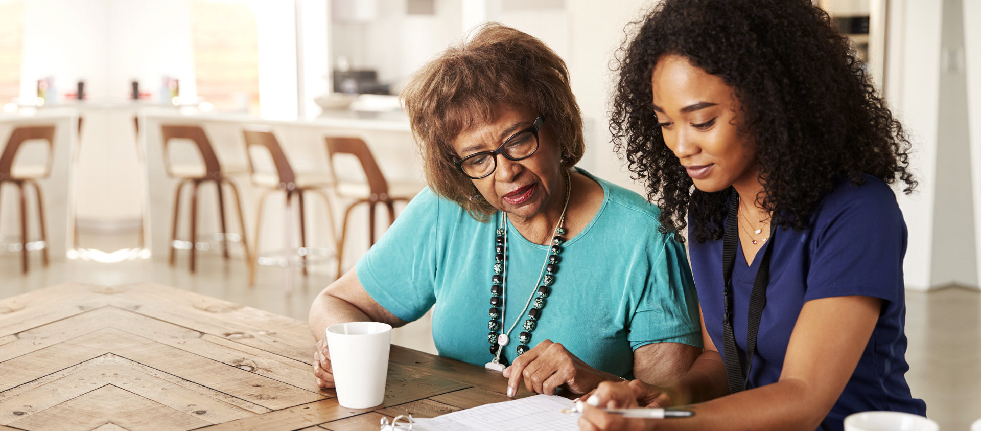 caregiver assisting senior woman in filling up a form